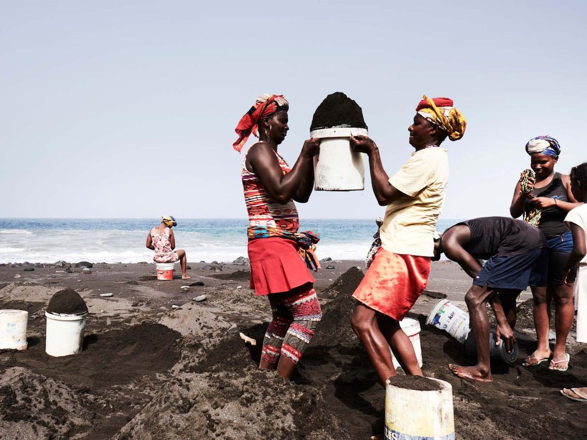Kübelweise tragen die Sandgräberinnen den Sand vom Strand.Hoffnung, auf Sand gebaut wie Gefährlich wird den Sandgräberinnen das Meer